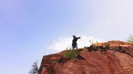 храбрость : Adult woman dances on a cliff edge .