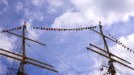 frigate : The masts of an old sailing ship against the sky.