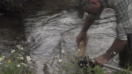 A man washes the trimmer in the creek. Stock Footage