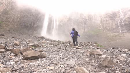 perçin : A woman with a backpack climbs up the rocks to the waterfall in hight mountains .. Stok Video