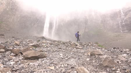 A woman with a backpack going down over stones from the mountains from a waterfall.