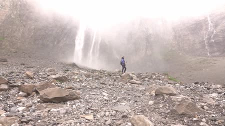 perçin : Waterfalls fall high in the mountains. A woman on a hike stops and touches the spray in air.
