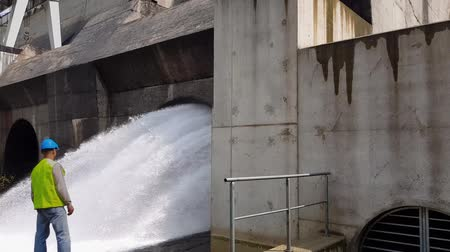 perçin : Cinemagraph (Photo-Motion) .A male worker stands in front of a stream of water from a hydroelectric turbine. Stok Video