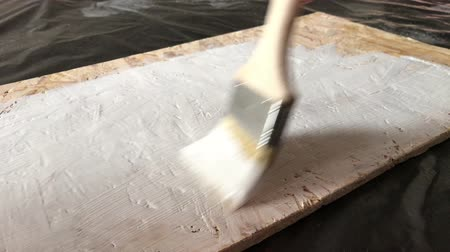 sörte : The process of painting a wooden shelf from OSB panel in white on a black background. Close-up of a flat wooden paint brush with white paint