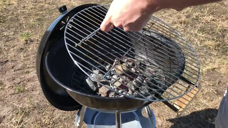 costela : Burning coals and wood on a grill grate. Preparation of coal for barbecue in a large round open grill. The concept of relaxation and enjoyment of food. Man puts the meat grill Stock Footage