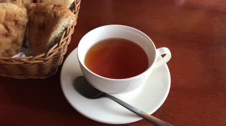 porcelán : A cup of black tea stands on a brown table, next to a basket of sliced bread. The camera approaches the cup. White tea pair with a spoon. Steam from hot tea