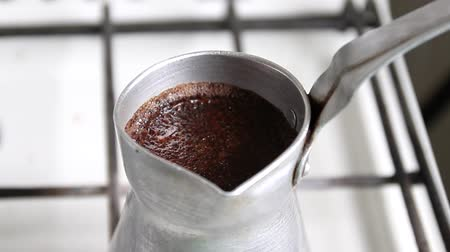kepçeli : Close up of cezve with aromatic coffee is prepared on the stove