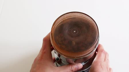 Womens hands hold a coffee grinder with brown fresh coffee grains and grind coffee to make a drink
