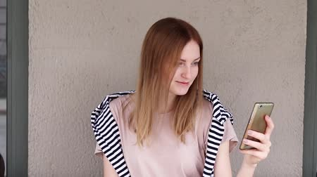 redhair : Young blonde girl makes selfie on a smartphone while sitting in a cafe Stock Footage