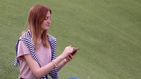 Young blonde girl talking on mobile phone sitting on a bench in a park