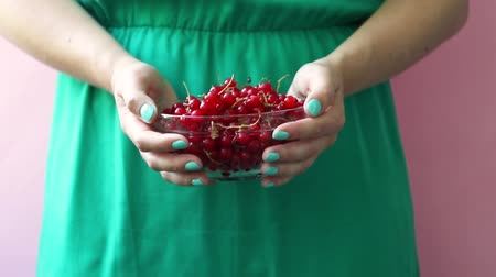 смородина : A girl in a green dress holds in her hands a glass bowl with red ripe currants on a pink background. Summer berry concept. Healthy eating Стоковые видеозаписи