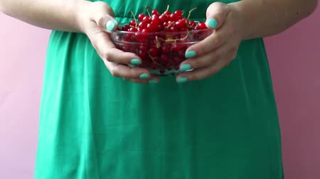 красная смородина : A girl in a green dress holds in her hands a glass bowl with red ripe currants on a pink background. Summer berry concept. Healthy eating Стоковые видеозаписи
