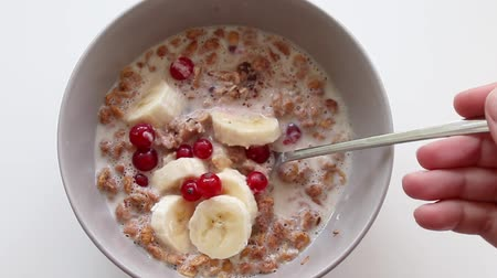 desamparado : Breakfast concept. Female hand interferes with oatmeal with berries and a banana in a plate. Stock Footage