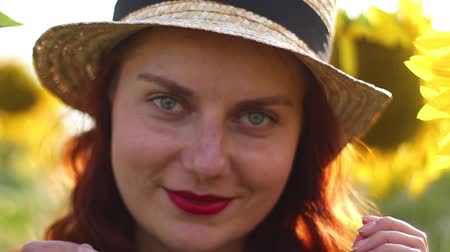 hair growth : A young red-haired girl in a straw hat and red lipstick smiles while looking at the camera. Huge yellow sunflowers field Stock Footage