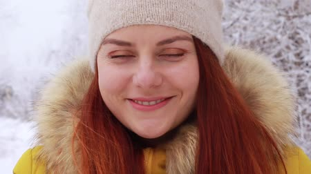 kafeterya : A young red haired girl in a warm knitted hat, yellow winter jacket drinks a hot drink from a metallic mug against the background of a winter landscape