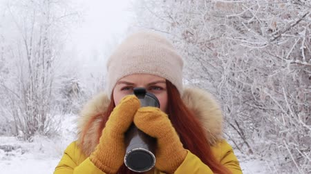 banka : A young red haired girl in a warm knitted hat, yellow winter jacket drinks a hot drink from a metallic mug against the background of a winter landscape