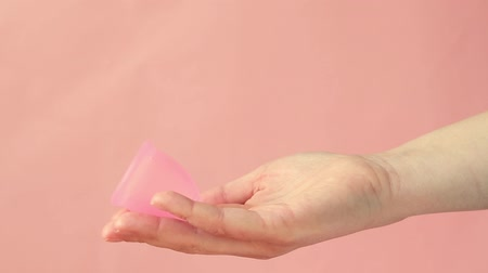 parte : Close up of a young woman hand holding reusable silicone menstrual cup. Zero waste menstruation concept. Stock Footage