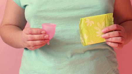bleeding : Young woman hands holding different types of feminine hygiene products menstrual cup and sanitary napkins. Women health concept, zero waste alternatives Stock Footage