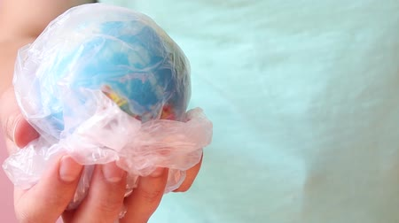 reutilizável : Save the planet concept. Female hand holds planet earth ball in a plastic bag. Global warming and plastic emissions. Zero waste Stock Footage
