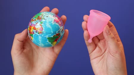 menstruáció : Zero waste. Save the planet concept. Global warming and plastic emissions. Female hand holds planet earth ball and menstrual cup. Stock mozgókép