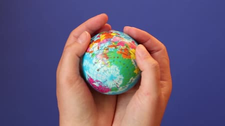 měsíčně : Save the planet concept. Global warming and plastic emissions. Female hand holds planet earth ball. Zero waste