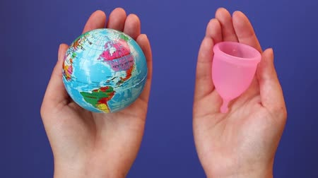 měsíčně : Save the planet concept. Global warming and plastic emissions. Female hand holds planet earth ball and menstrual cup. Zero waste