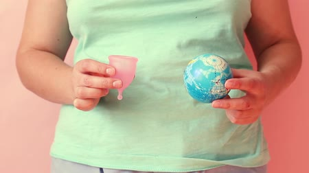 menstruáció : Global warming and plastic emissions. Female hand holds planet earth ball and menstrual cup. The silicone feminine hygiene product is an eco-friendly, sustainable, zero waste alternative to pads or tampons. Stock mozgókép