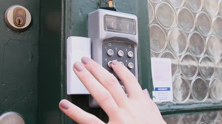 errado : Woman dials a code of intercome and opens a door of a house. Security door with a number dial pad