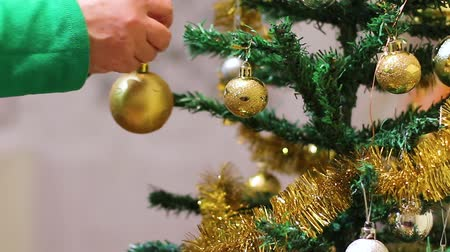 x mas : Female hand broadcasts Christmas ball decoration to the Christmas tree on New Years Eve. Holiday home decoration