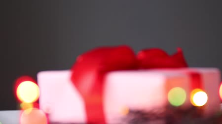 envolto : Beautiful surprise gift box with red bow and blurry lights garland on the table. Holiday composition video Vídeos