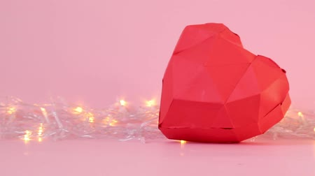 оригами : Paper cut red geometric 3d heart shape with golden lights garland on a pink background. Valentines Day concept