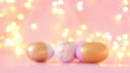 pascha : Gold and pink eggs pattern on a light blurry garland. Shallow depth of field. Holiday concert
