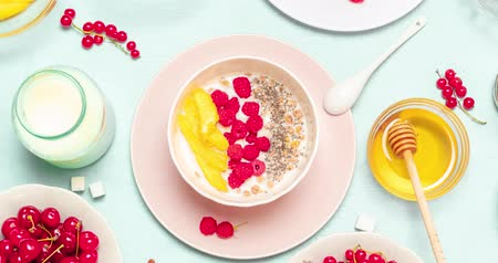клюква : Granola cereal with chocolate, , mango, raspberries, chia seeds and milk in a pink ceramic bowl on a blue background. Proper nutrition, diet and delicious breakfast concept.