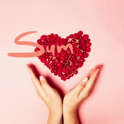 blackberry : Love shape made from red fruits on a pink background. Red currants, strawberries, strawberries, cherries and female hands. Minimal composition with the inscription summer