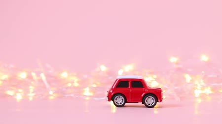 geçen : Red childrens toy car rides and a golden blinking garland on a pink background. Delivery concept Stok Video