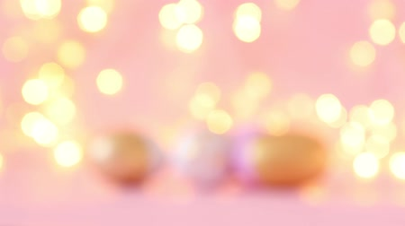 zaproszenie ślubne : Gold and pink eggs pattern on a light blurry garland. Wideo