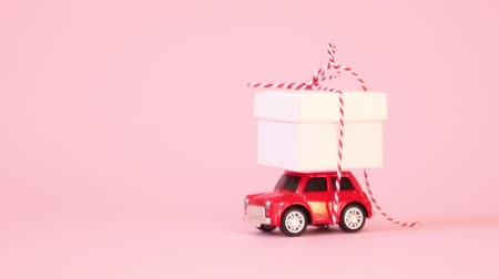 metáfora : Red retro toy car delivery gift box with ribbon bow on a pink background. Colorful confetti falls on a car. Birthday, Valentines Day, Womens Day concept.