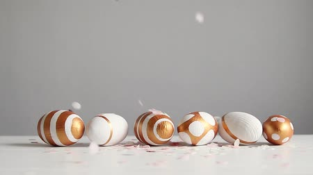 původní : Easter golden and white decor eggs on a white background with place for text. Festive multi colored confetti falls on the table.