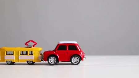 colision : Yellow tram toy model and red auto toy collision on a white background. Road accident. Frontal collision of a motor vehicle and public transport.