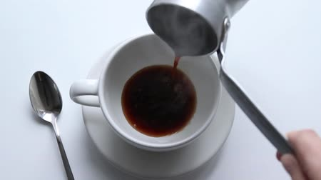 turk : Female hand pours strong hot coffee with a white ceramic cup made of aluminum cezve. Morning hot drink for invigorating