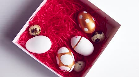 fürj : White gift box with red confetti decorated with golden eggs and quail eggs on a white table. Female hand takes eggs from the basket Stock mozgókép