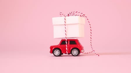 давать : Red retro toy car delivery gift box with ribbon bow on a pink background. Birthday, Valentines Day, Womens Day concept. Стоковые видеозаписи