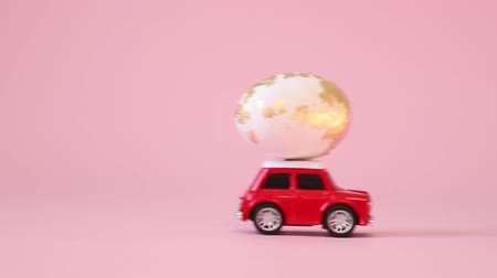 pascha : Red toy model car with a golden pattern egg on a pink background. Happy easter concept. Gift delivery. Wideo