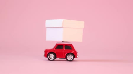 geçen : Red retro toy car delivery gift box with ribbon bow on a pink background. Birthday, Valentines Day, Womens Day concept. Stok Video