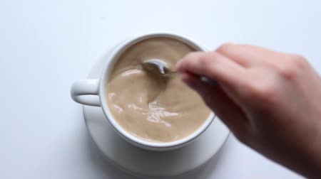 csészealj : Female hand interferes with a metal spoon a hot drink. Latte or coffee with milk in a ceramic white cup on the table, top view
