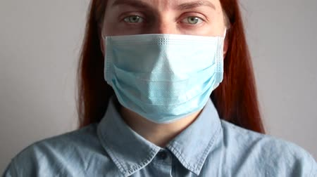 influenza background : Red-haired girl in medical mask looks into the camera. Allergy, headache. Stock Footage