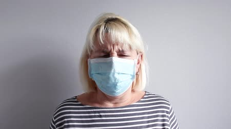gorączka : Adult blonde woman in a medical mask coughs. Virus or common cold concept
