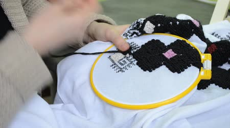 The woman embroiders by hand Ukrainian embroidery on white fabric with black wool threads in the hoop, right view