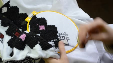 The woman embroiders by hand Ukrainian embroidery on white fabric with black wool threads in the hoop, left view