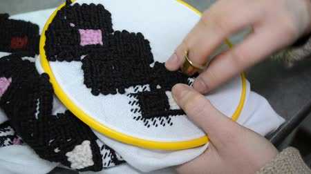 nativo : The woman embroiders by hand Ukrainian embroidery on white fabric with black and pink wool threads in the hoop, left view closeup
